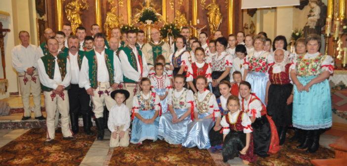 Zdjęcie grupowe członków zespołu folklorystycznego Śpis wykonane w kościele parafialnym w Nowej Białej wraz z księdzem proboszczem Tadeuszem Korczakiem
